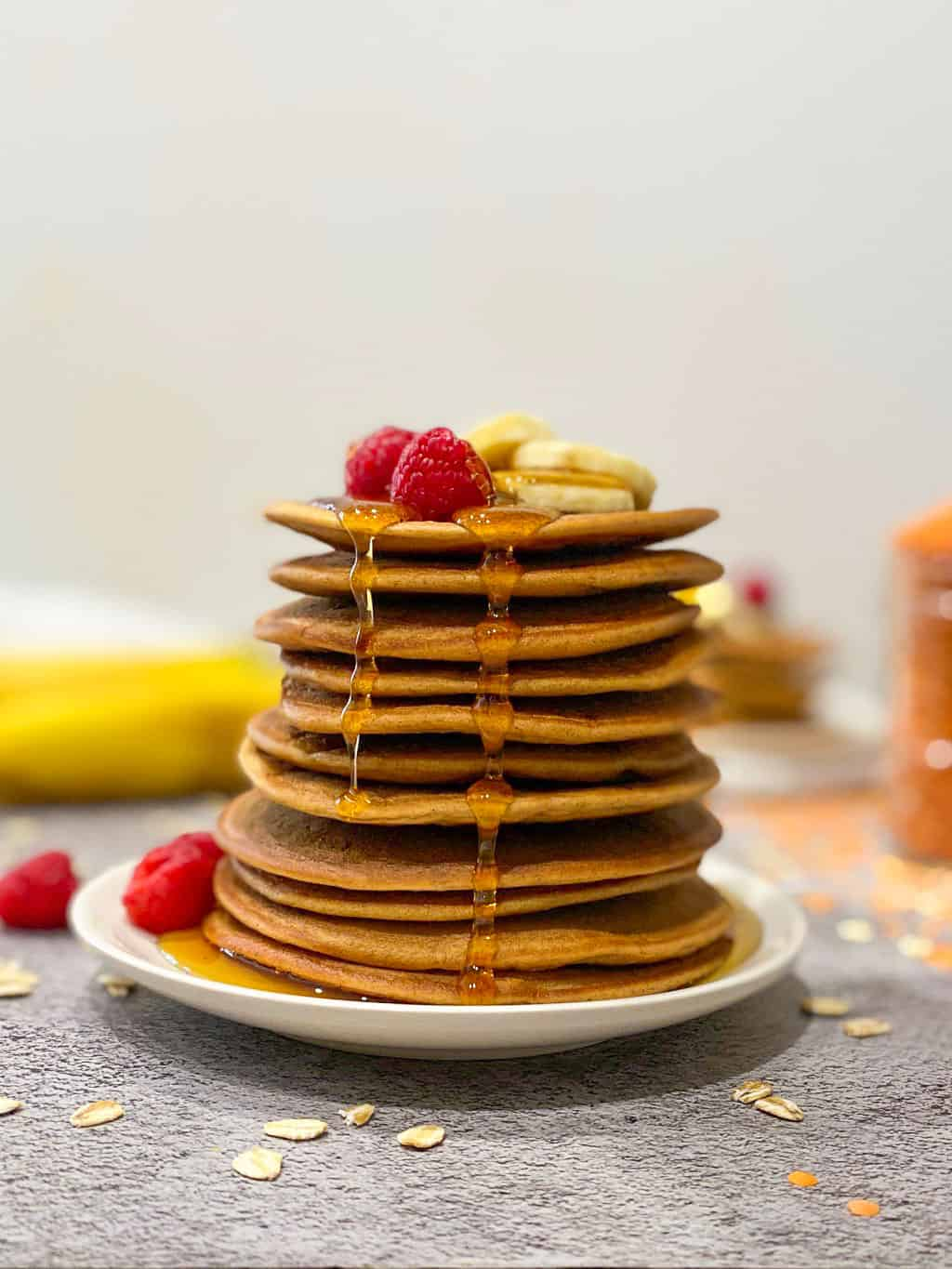 Stack of pancakes with maple syrup dripping down the sides and berries on top.