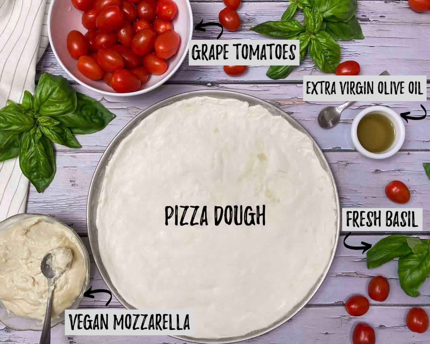 pizza dough stretched onto tray with bowl of tomatoes, cup of olive oil, bowl of vegan cheese and basil scattered around