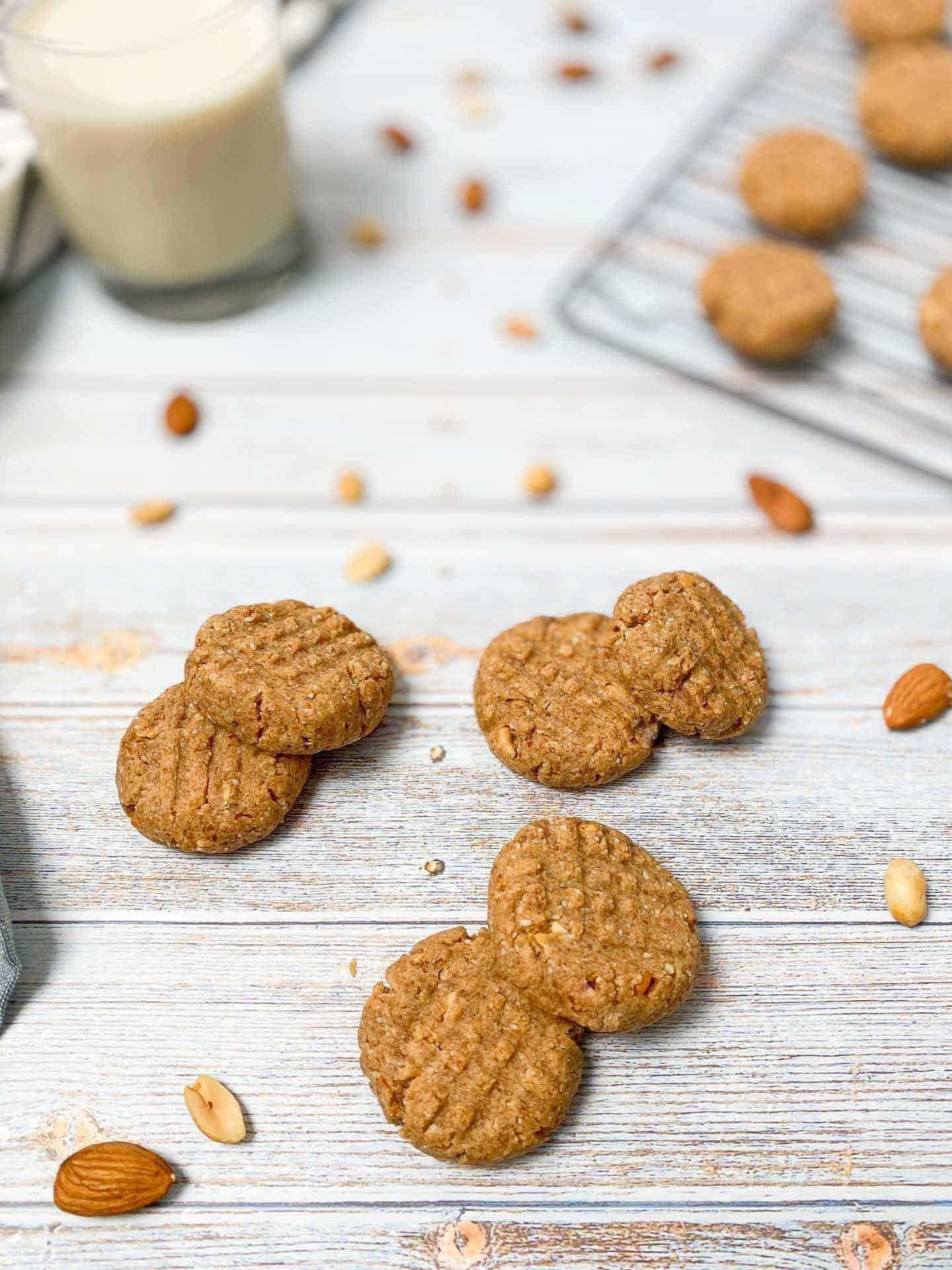 peanut butter almond cookies scattered on deck with glass of milk in background