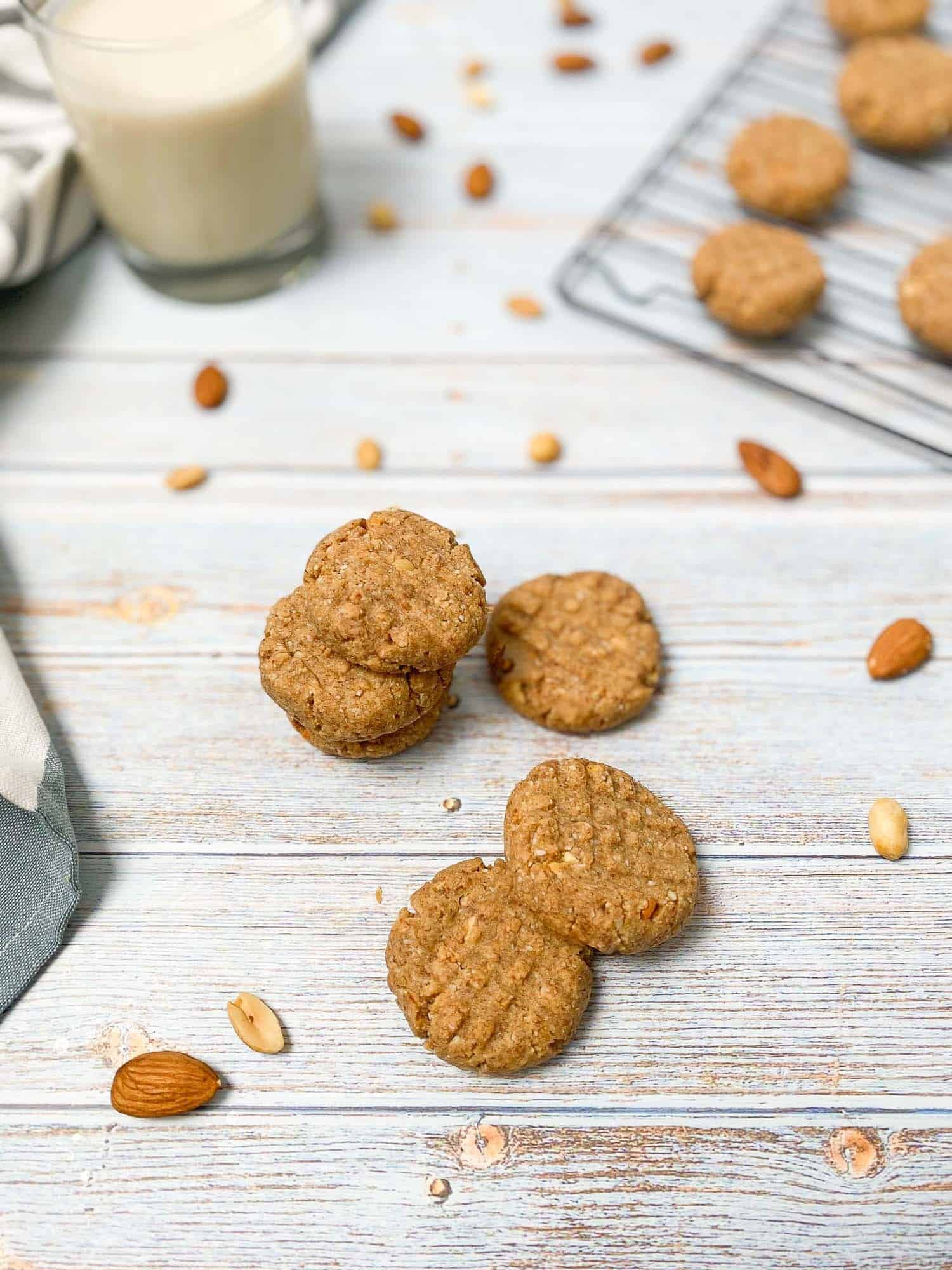 peanut butter almond cookies scattered on deck with peanuts and almonds around them