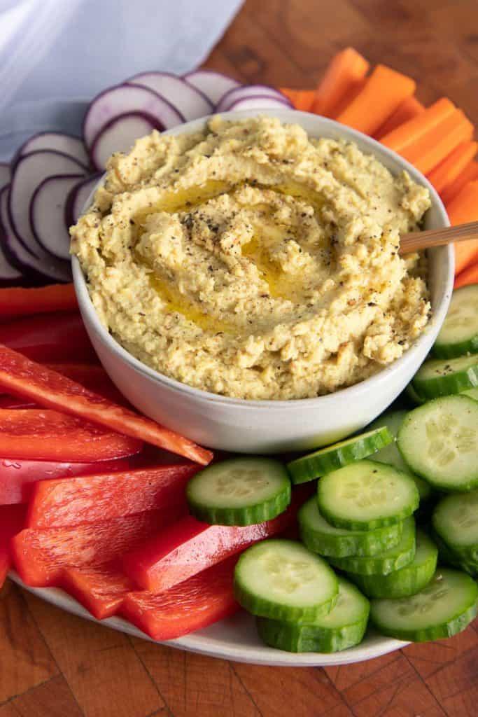 white bowl of cauliflower hummus with raw veggies surrounding it