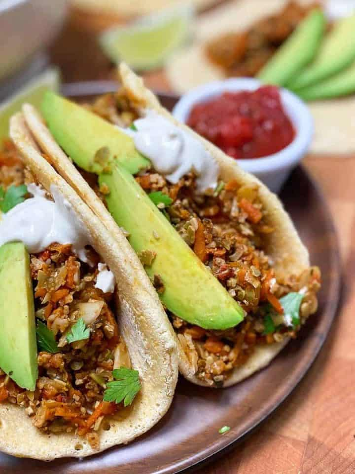 soft tacos on plate with avocado garnish and salsa for dipping