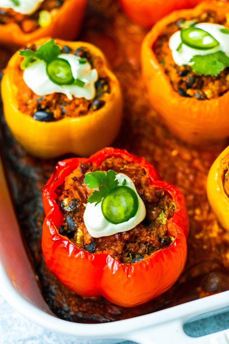 stuffed peppers in baking dish with black beans, sour cream and jalapeno on top