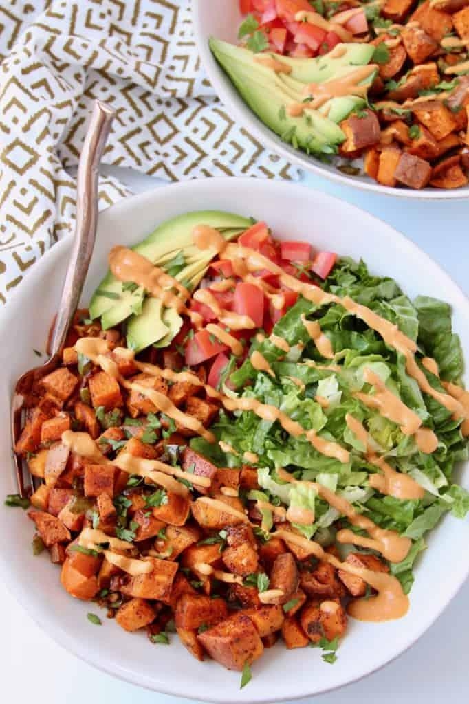 white bowl with sweet potato, lettuce, tomato, avocado and chipotle sauce