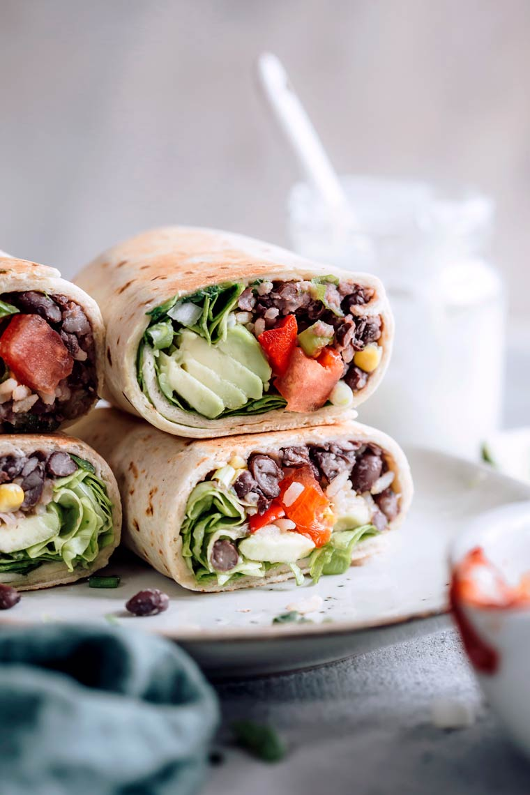 bean burritos stacked on plate with beans, tomato and avocado