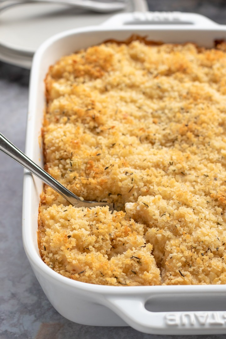 Casserole dish filled with shredded cauliflower and vegan cheese with serving spoon inside.