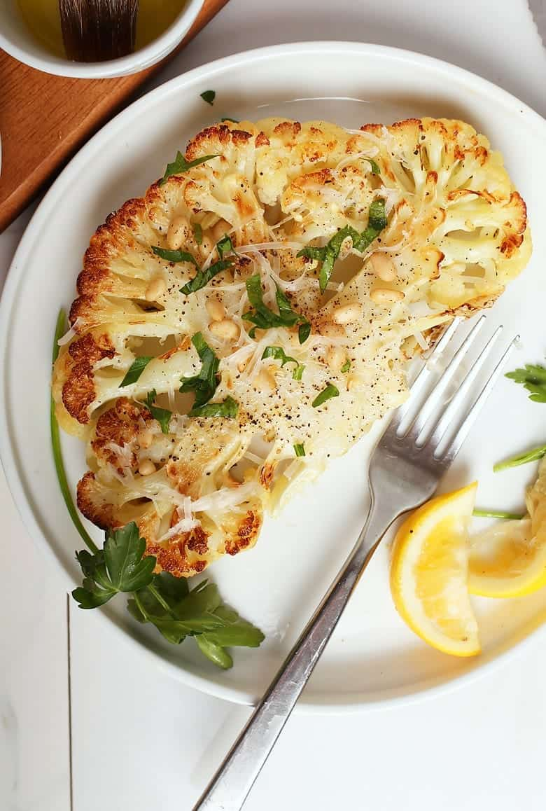 """White plate with cauliflower """"steal"""" and herbs on top with fork on the side."""