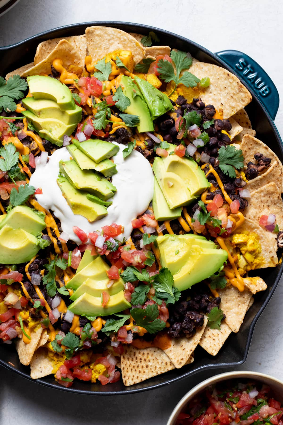 pan of nacho chips with beans, vegan cheese, tofu scramble, avocado and sour cream on top