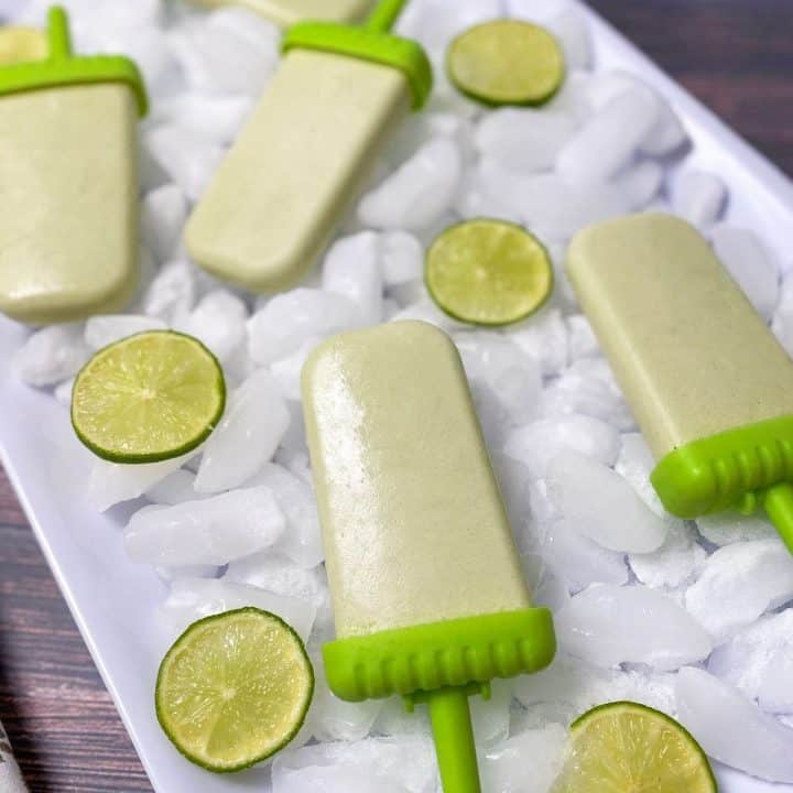 white tray of ice with coconut lime popsicles on top