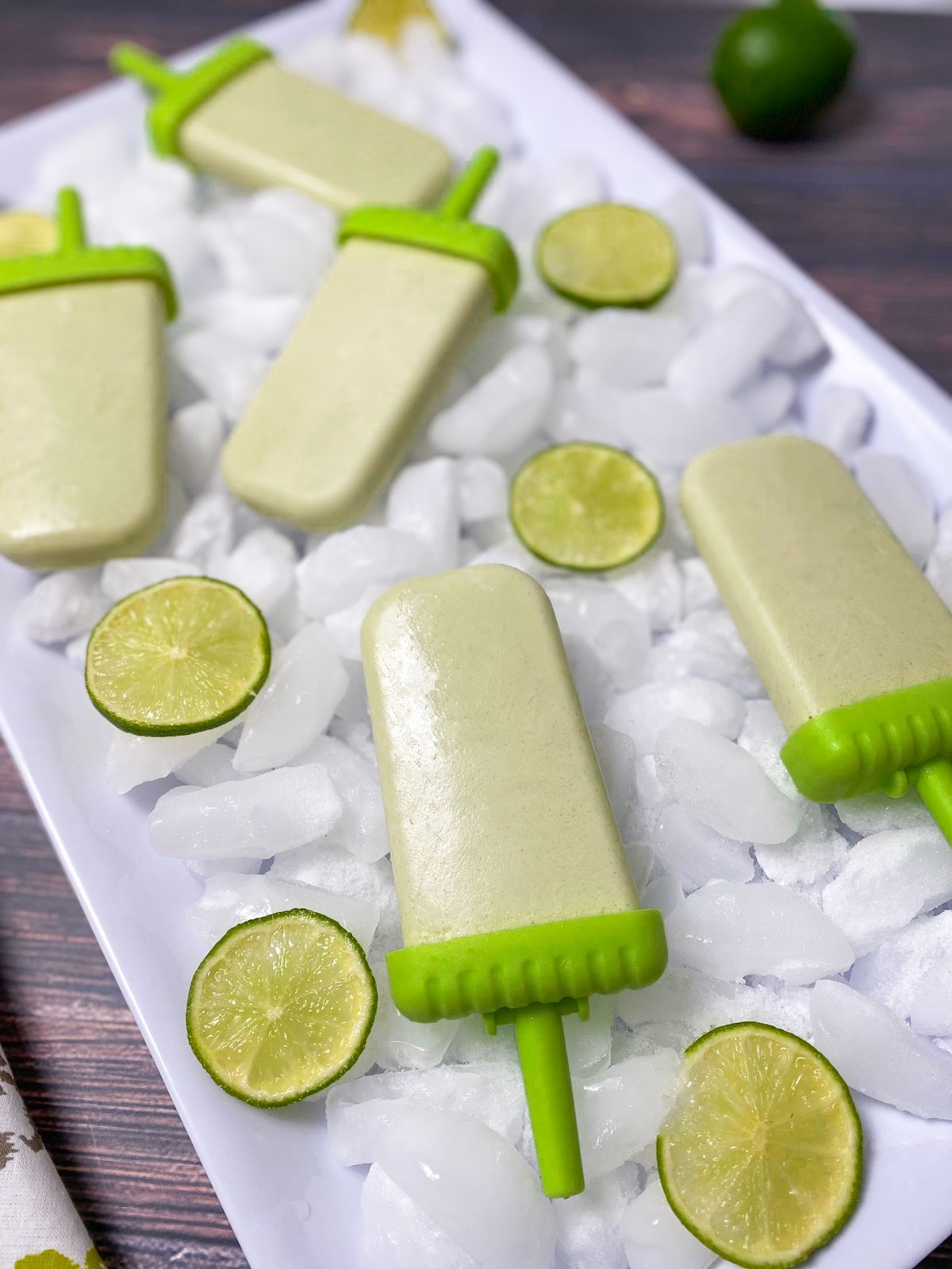 coconut lime popsicles on white tray of ice with lime slices around them