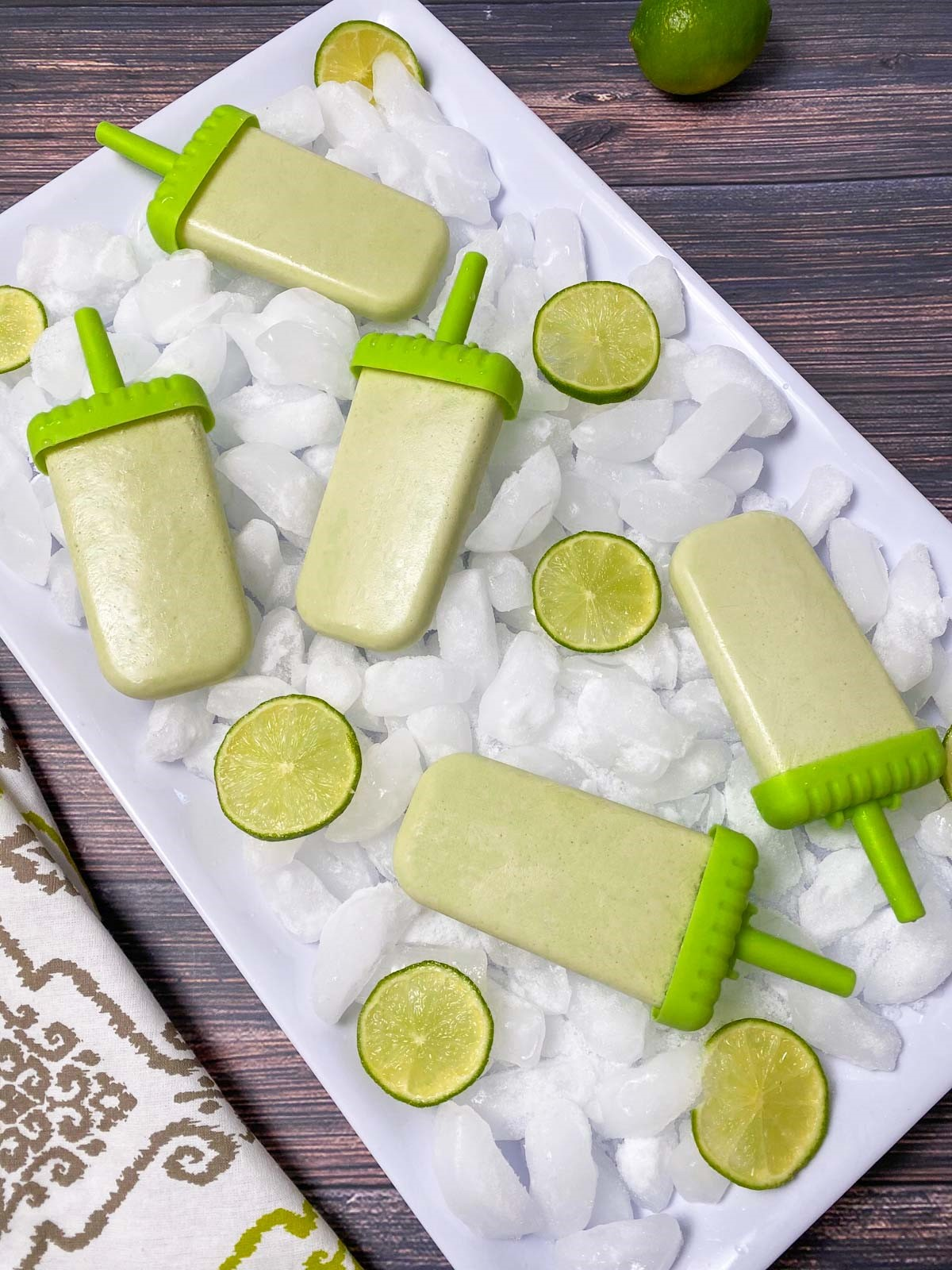 white rectangular tray filled with ice, lime slices and popsicles