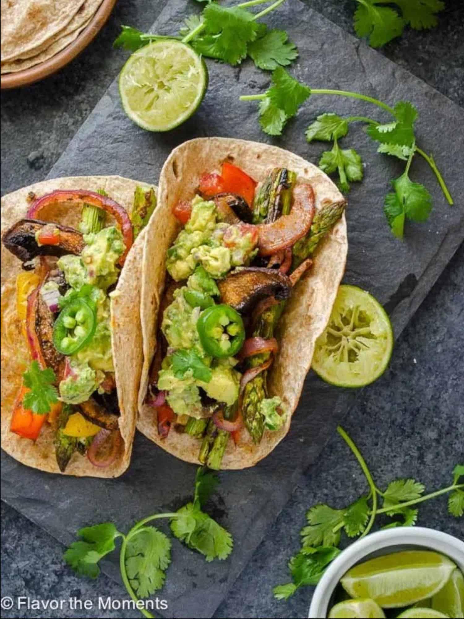mushroom and asparagus inside taco shells with lime and cilantro garnish around them.