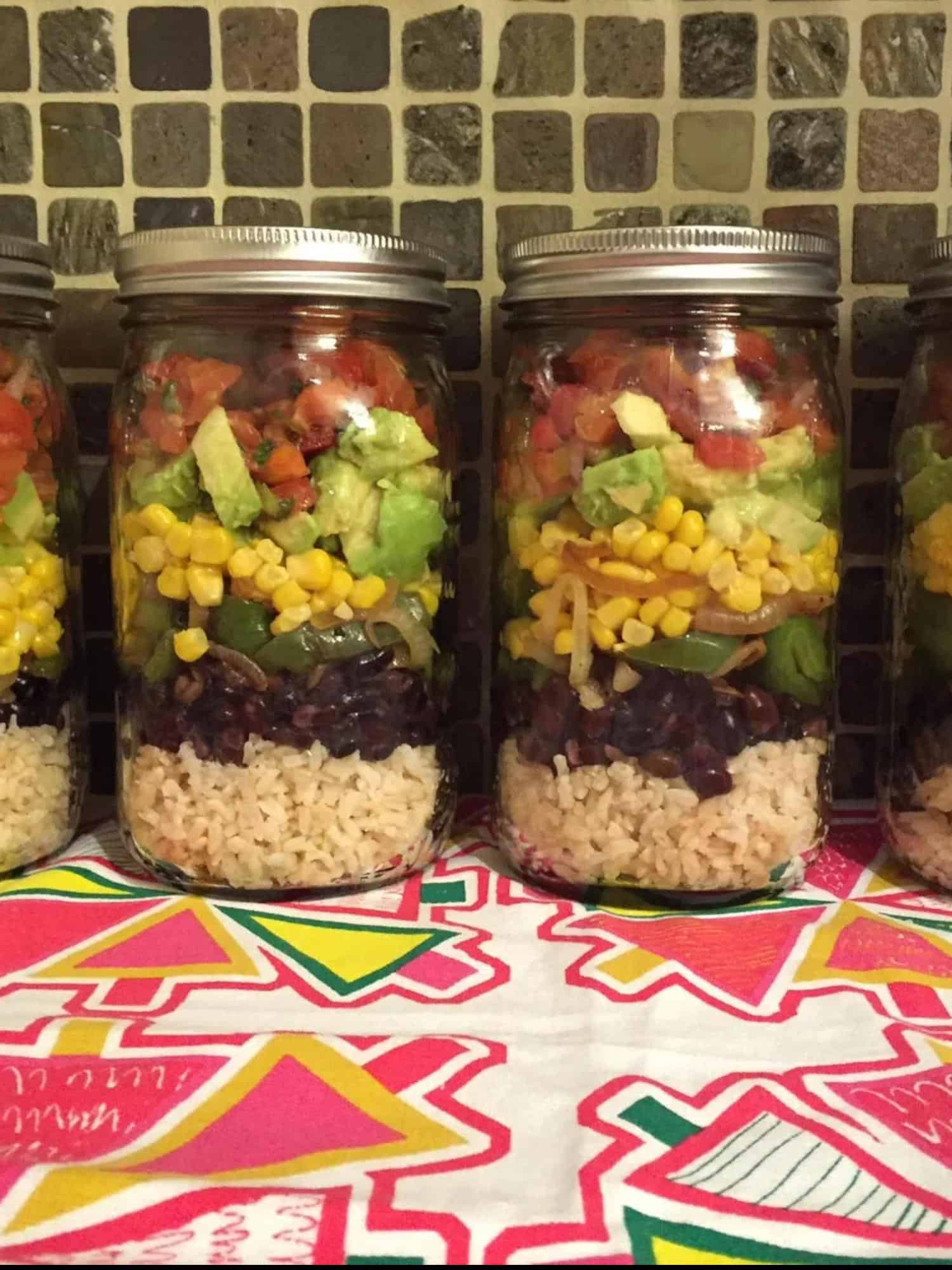 mason jar layered with rice, beans, corn, avocado and tomato.