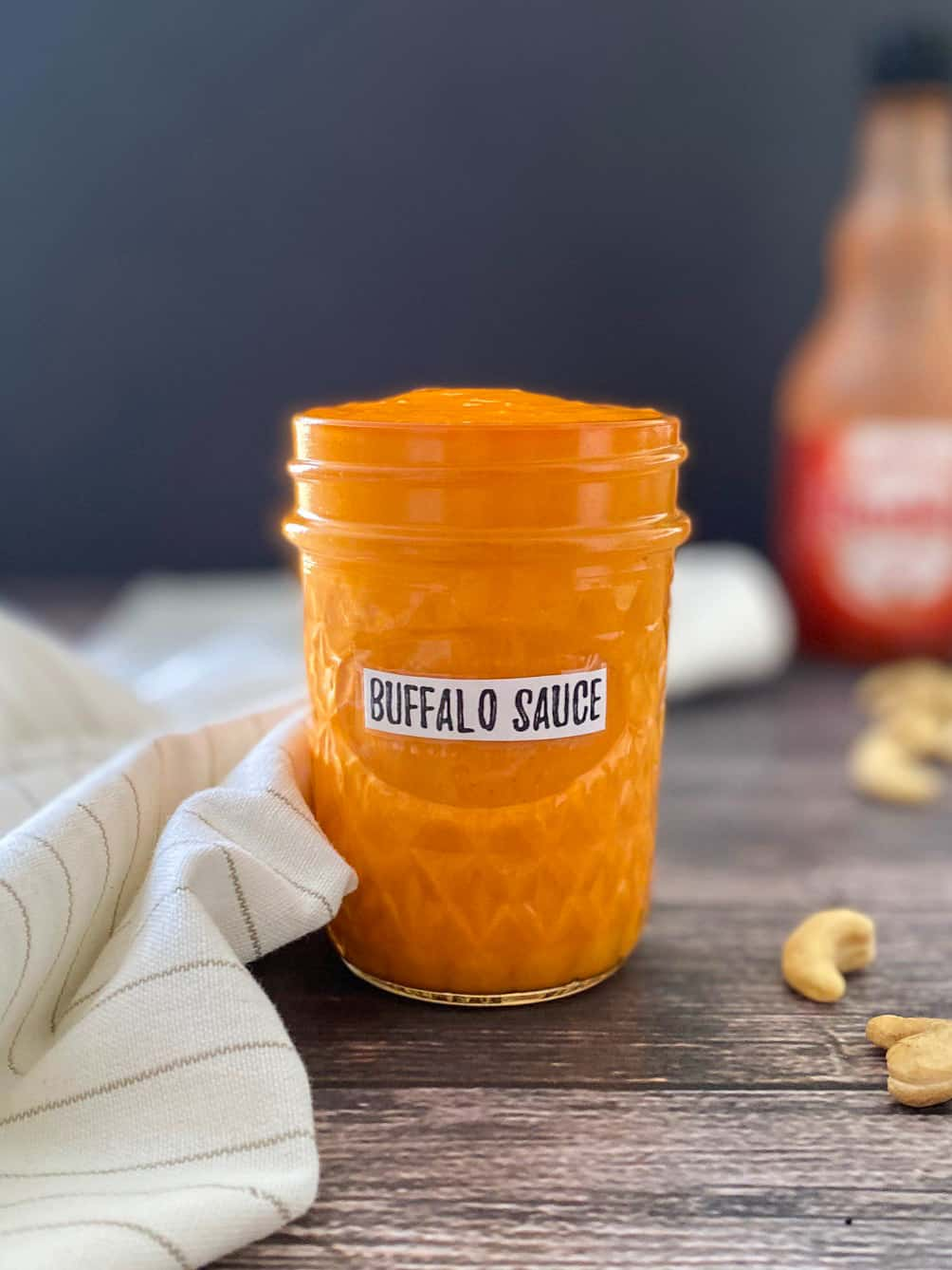 glass jar filled with orange hot sauce with bottle of Frank's RedHot in the background