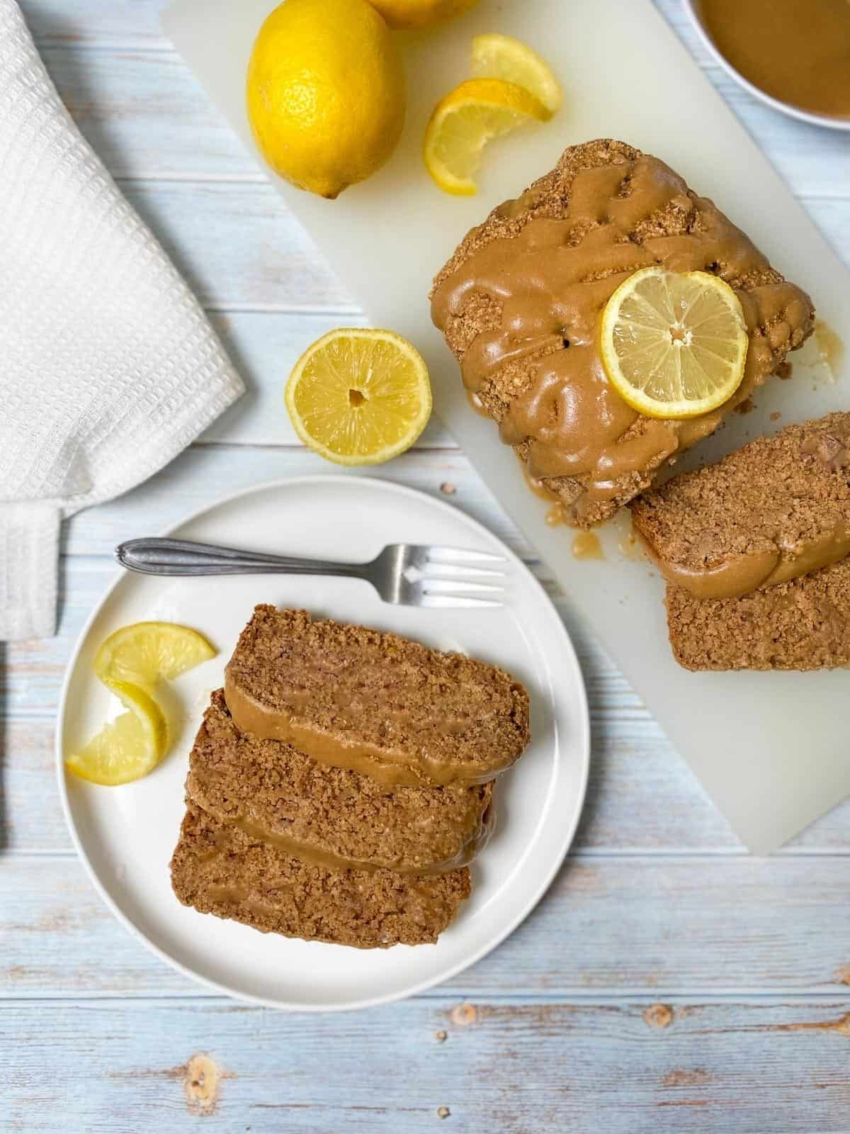 slices of lemon bread in white plate with remaining loaf beside it on white cutting board