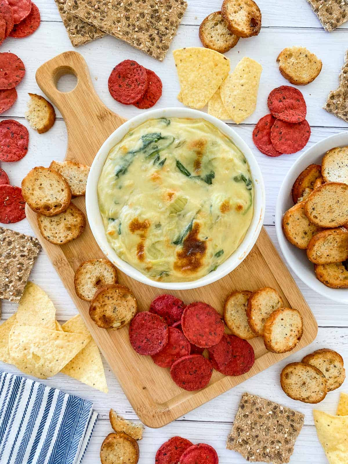 spinach dip in oven safe dish after broiling with crackers and chips scattered around the dip