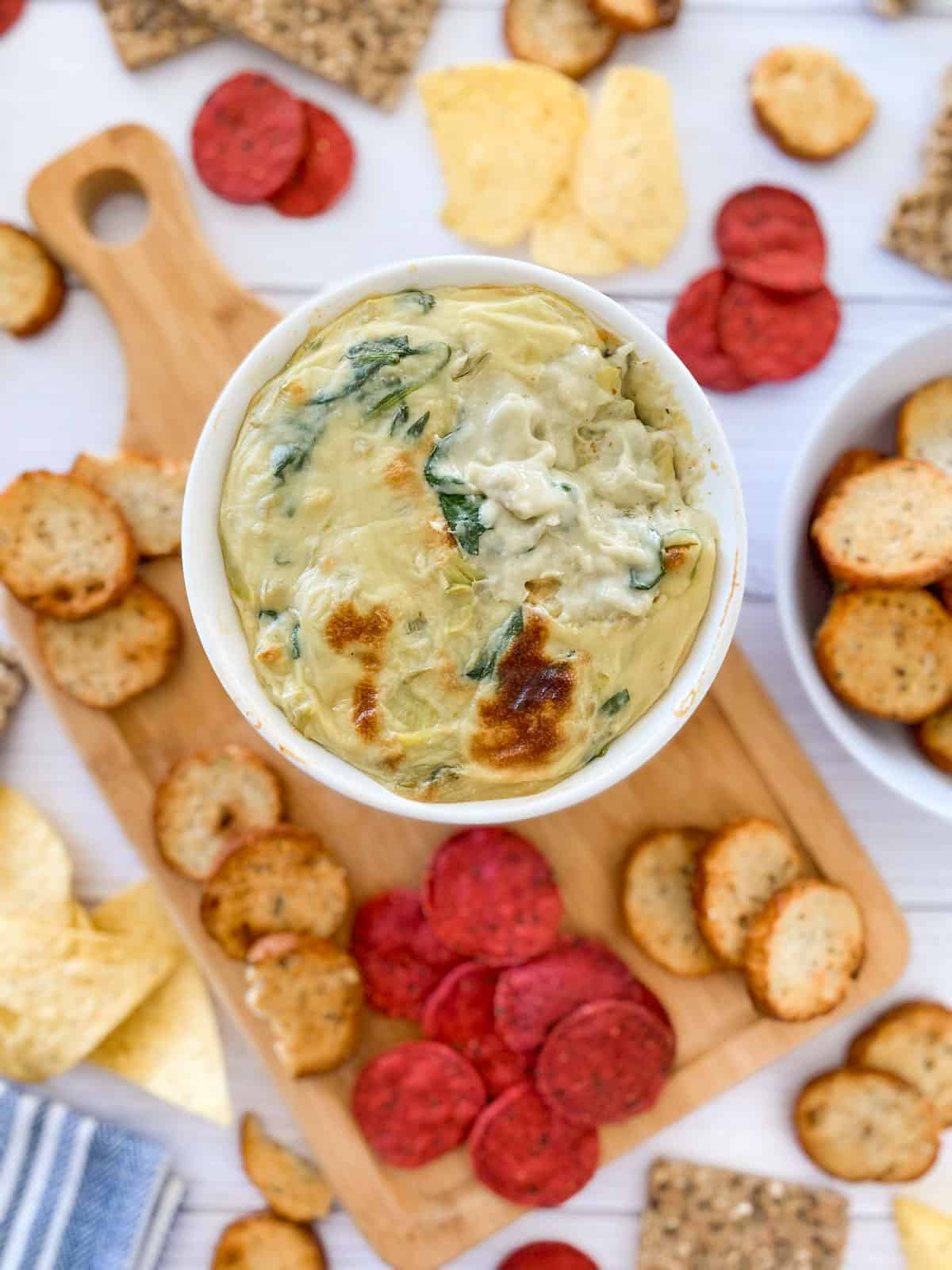 Bowl of vegan spinach dip with crackers and chips scattered around it.