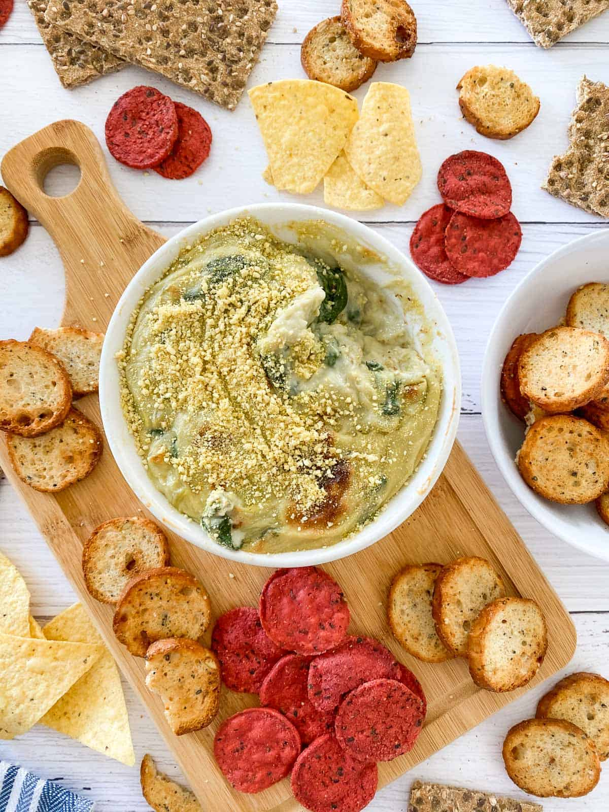 bowl of dip with parmesan garnish on top and crackers and chips scattered around the bowl