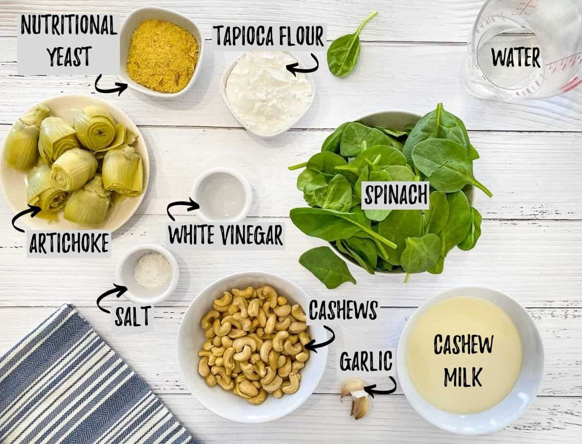 ingredients to make vegan spinach artichoke dip on white deck