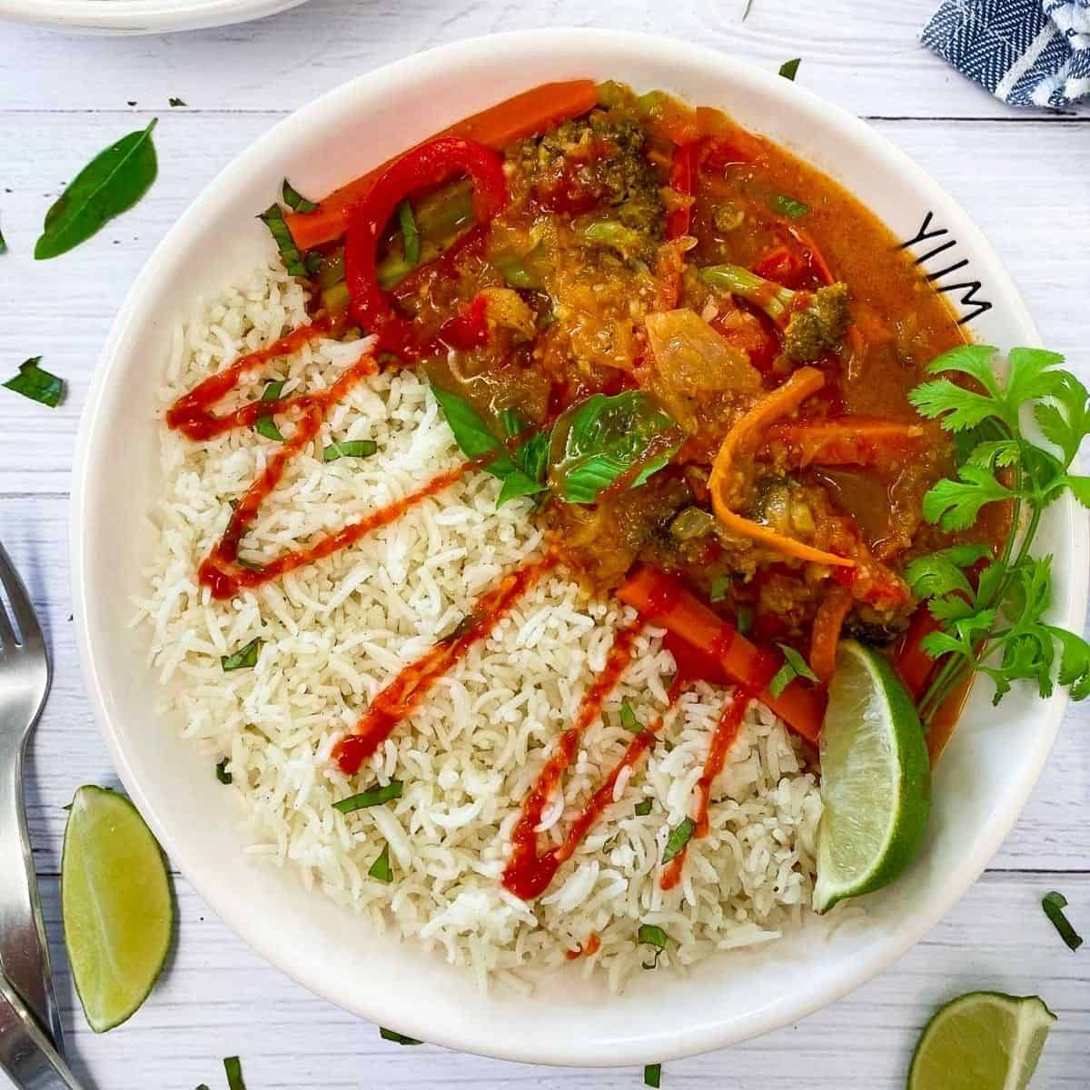 white bowl with rice, thai curry and drizzled in hot sauce