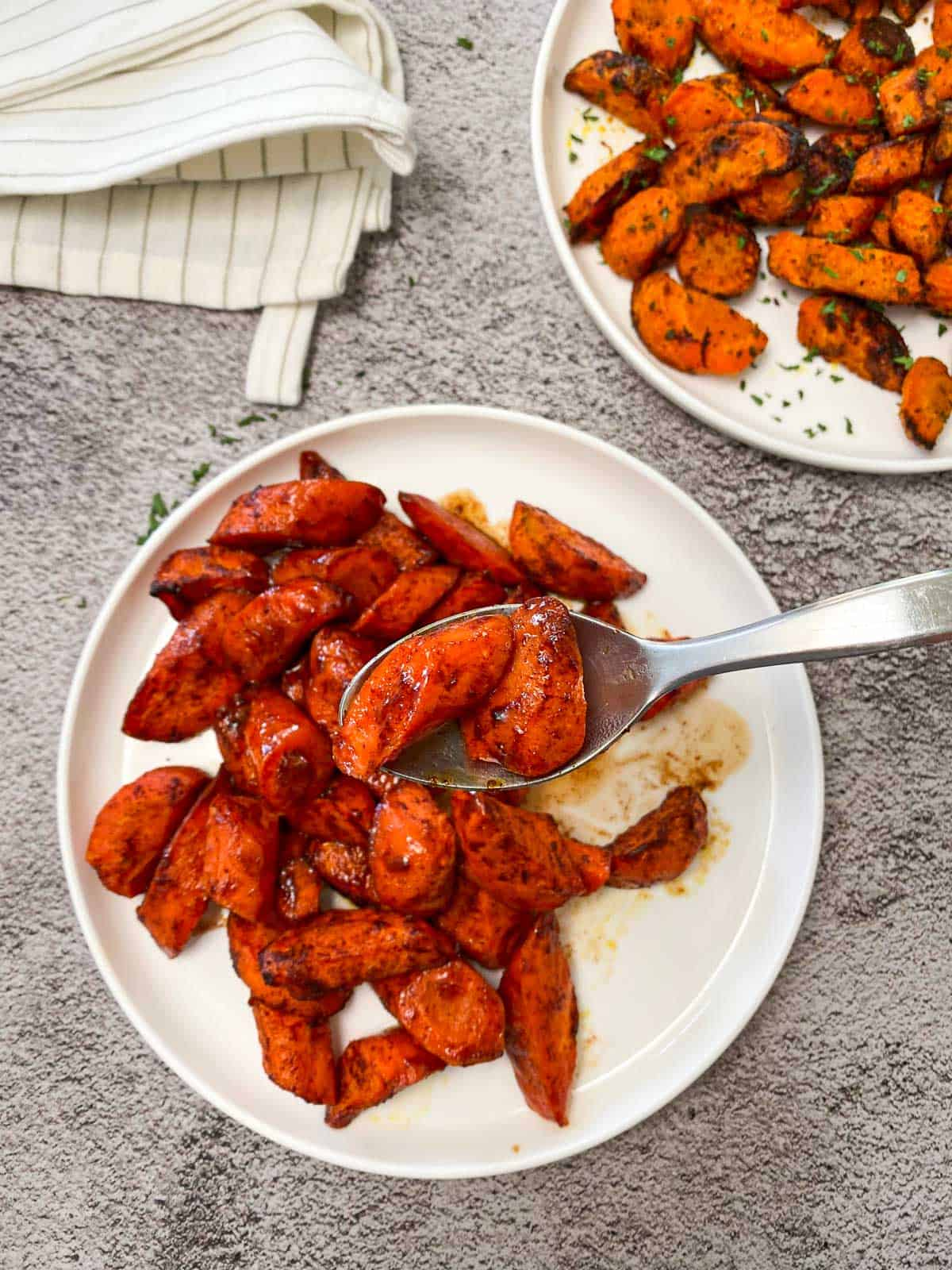 air fryer sweet carrots in white serving dish with spoon holding up two pieces of the carrots