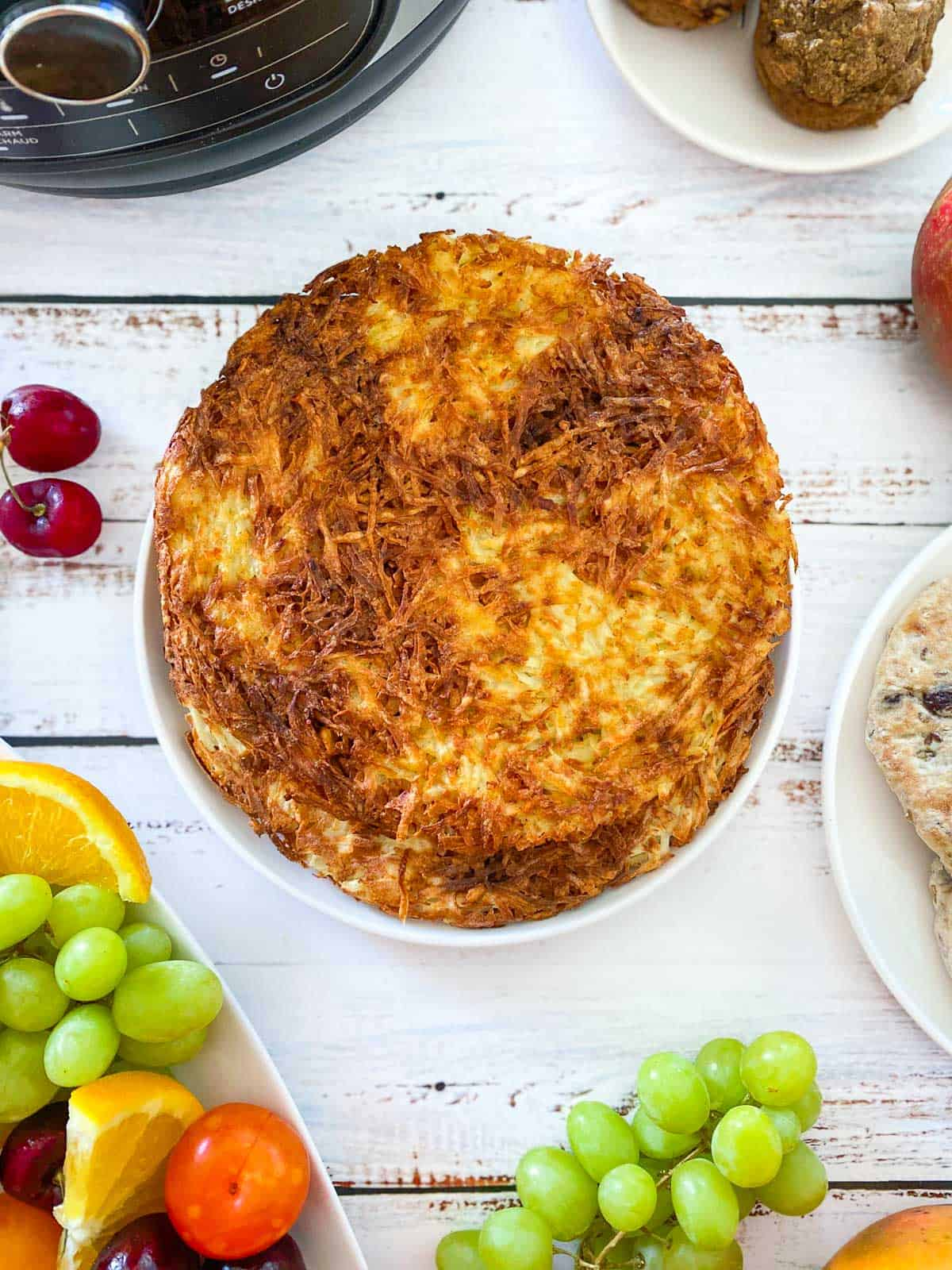 large round hash browns in plate with air fryer in the background and fruit scattered around