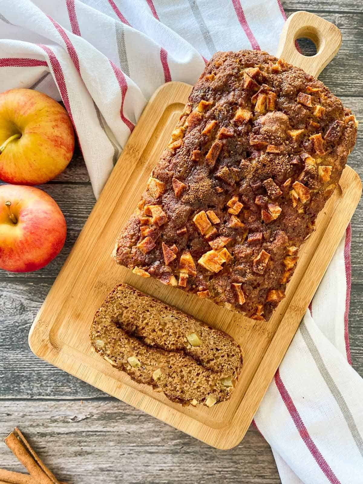 wooden cutting board with apple loaf on top with one slice cut.