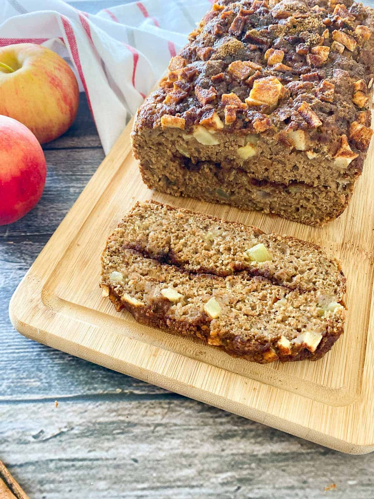 close up of vegan apple bread on cutting board with one slice laying on its side.