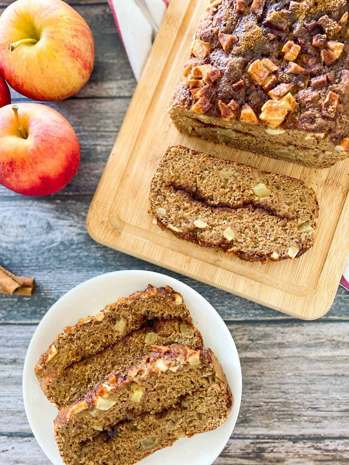 two slices of vegan apple bread on white plate with remaining loaf on cutting board and apples on the side.