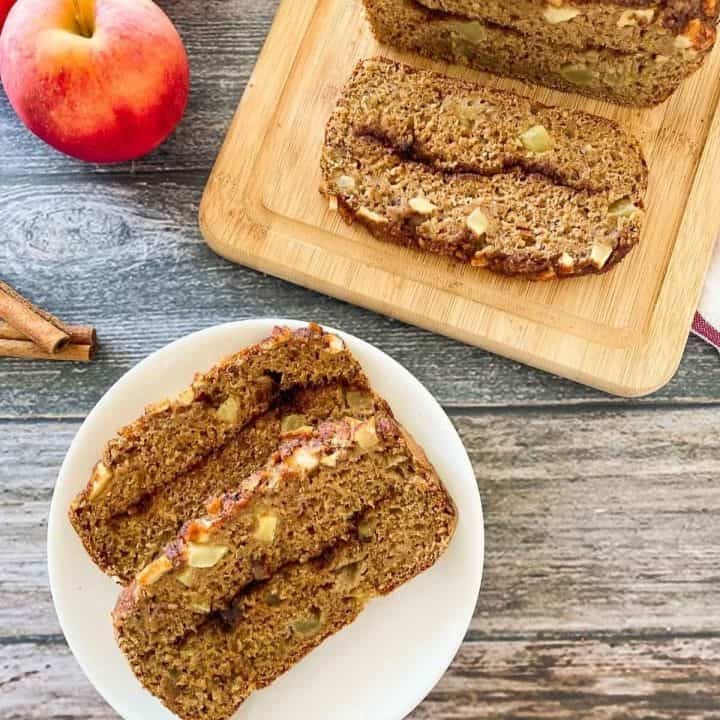 apple bread on cutting board and plate in front of the loaf with two slices on it.
