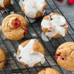 vegan raspberry muffins with white glaze on cooling rack