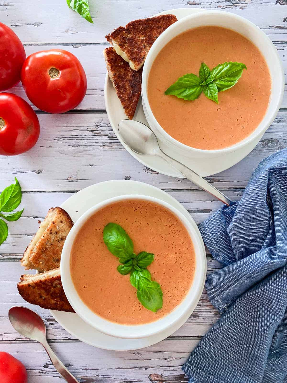 two white bowls filled with tomato soup with grilled cheese on the side