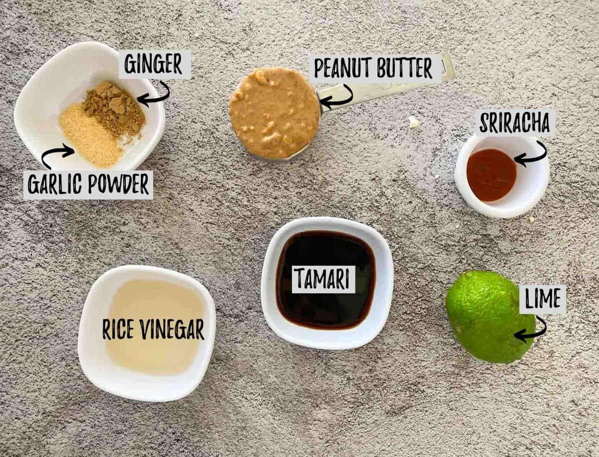 Ingredients needed to make peanut sauce in small prep bowls on concrete surface.