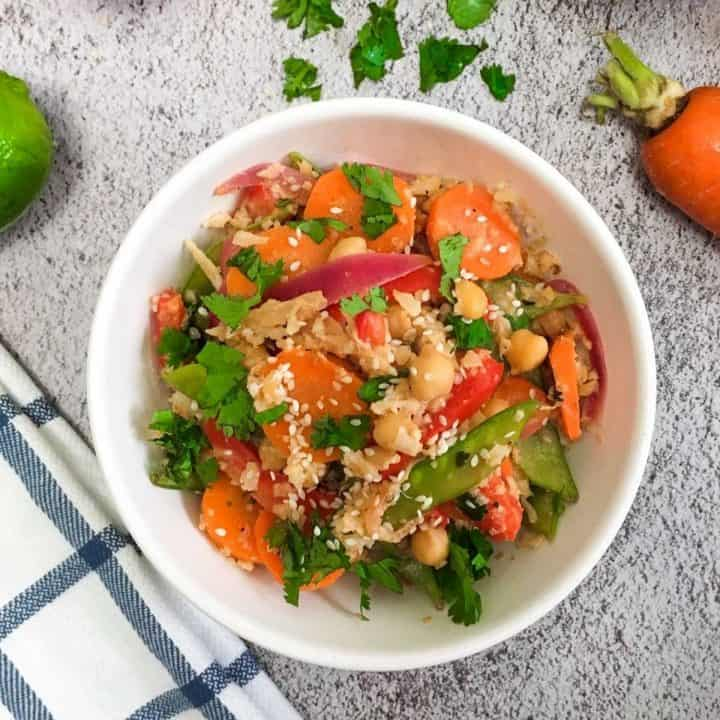 White bowl of cauliflower rice and vegetables in peanut sauce.