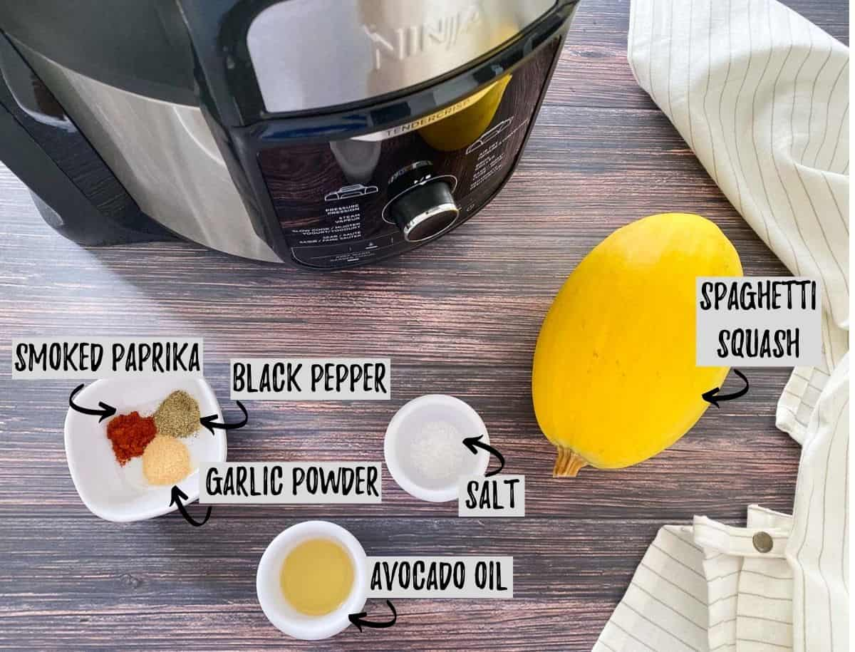 ingredients required to make air fryer spaghetti squash scattered on brown deck.
