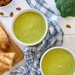 two white bowls of green soup with broccoli and almonds in background.