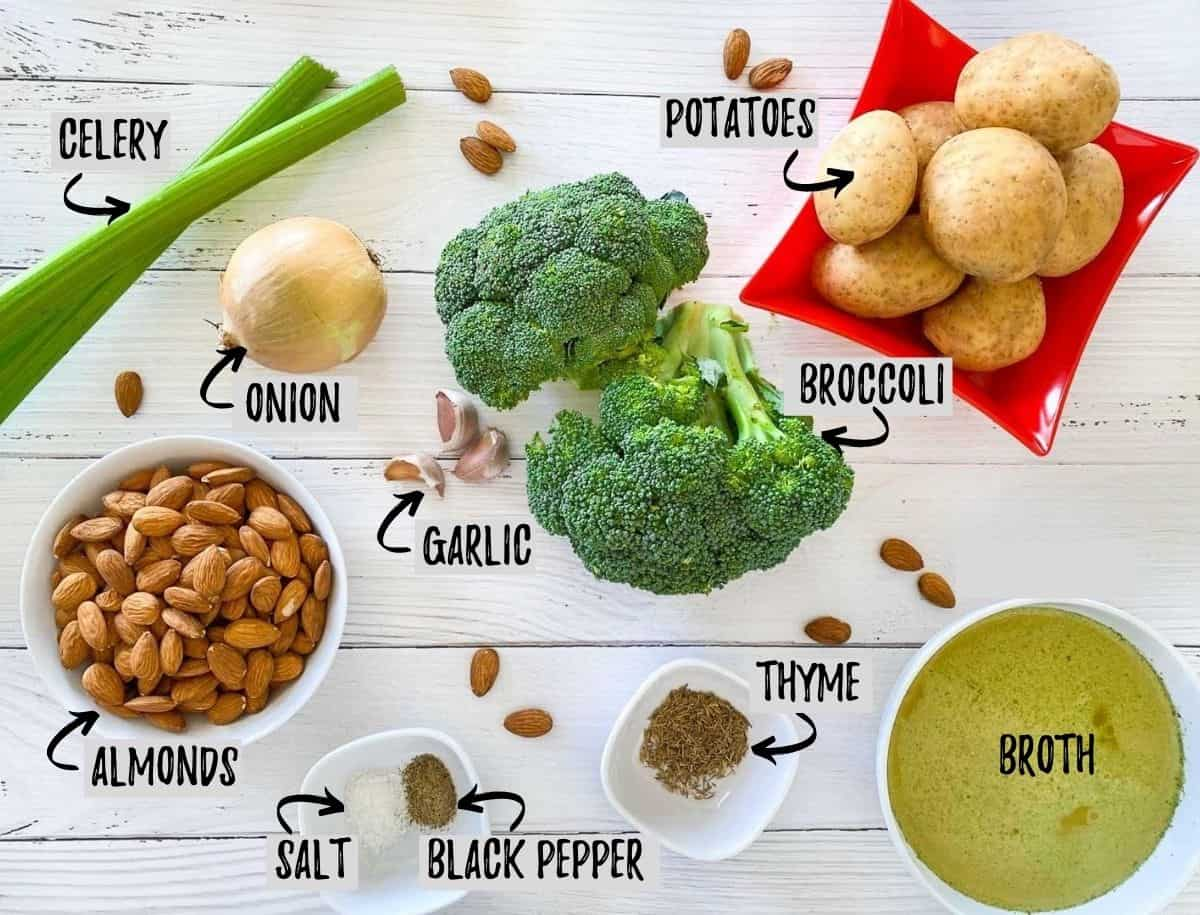 ingredients to make broccoli almond soup scattered on white deck.