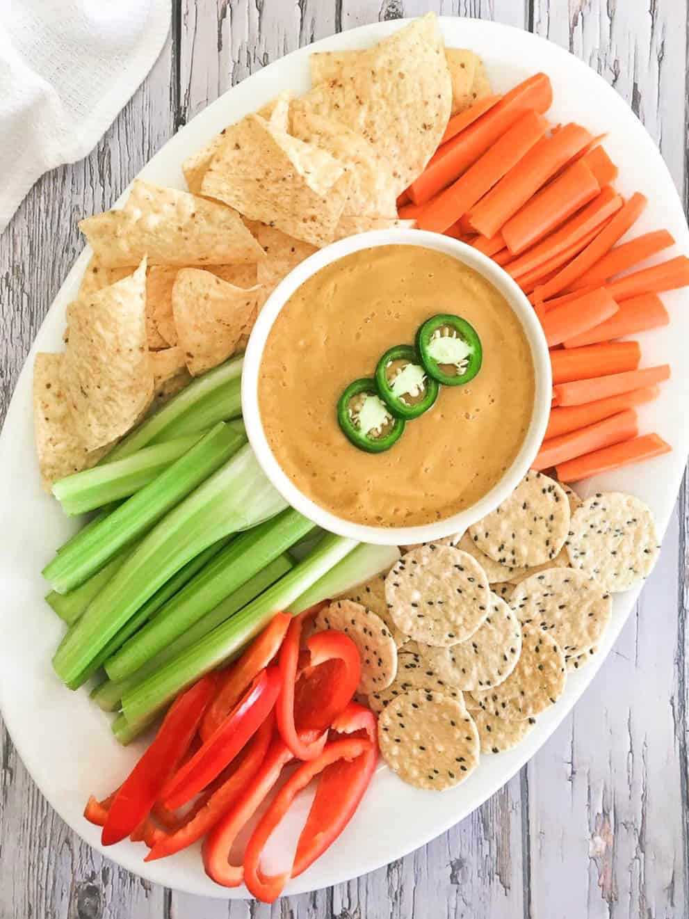 Platter with carrots, peppers, celery, chips and crackers and dip in the middle.