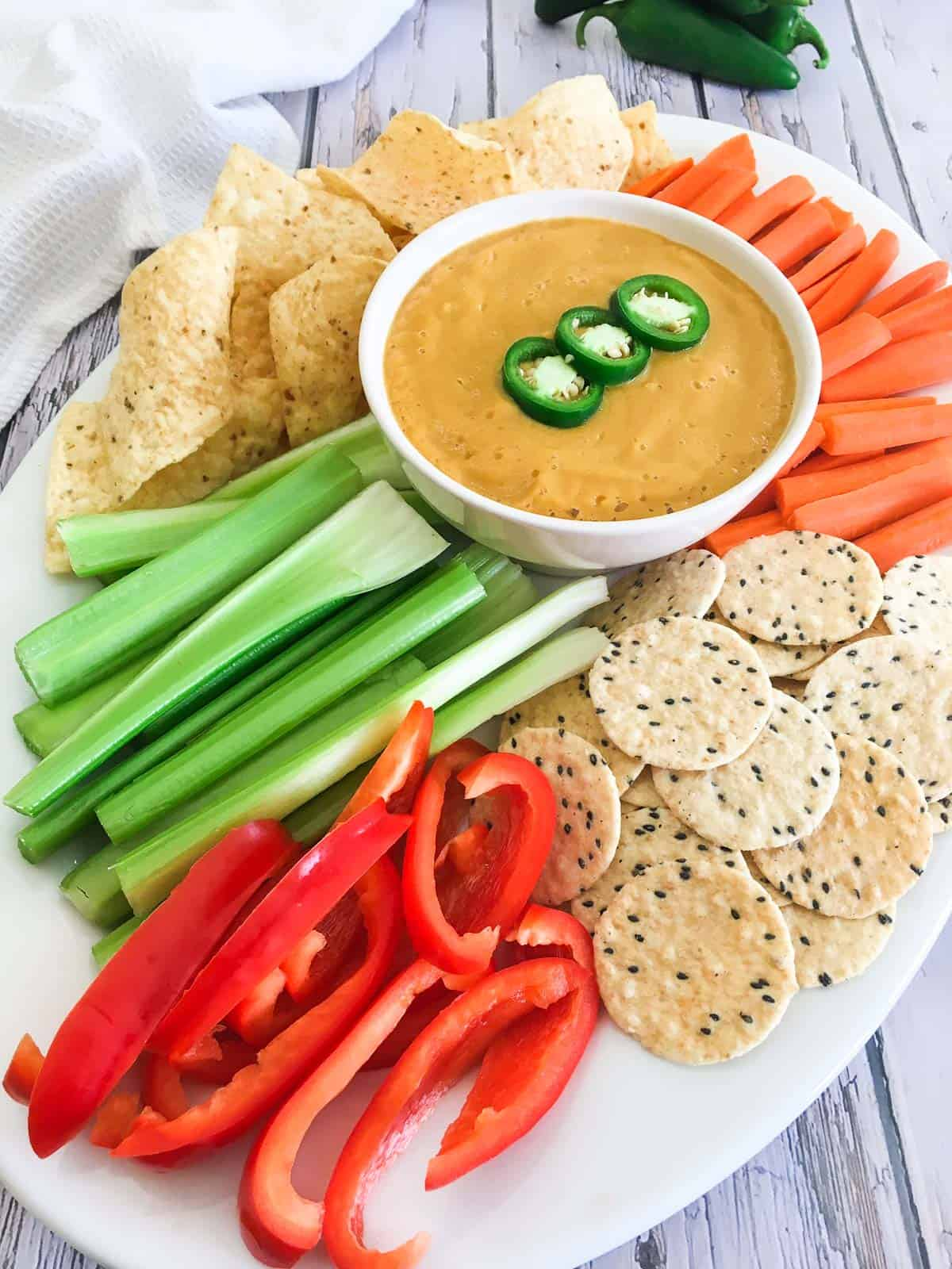 Platter of chips, crackers and veggies with bowl of vegan cauliflower dip in the middle.