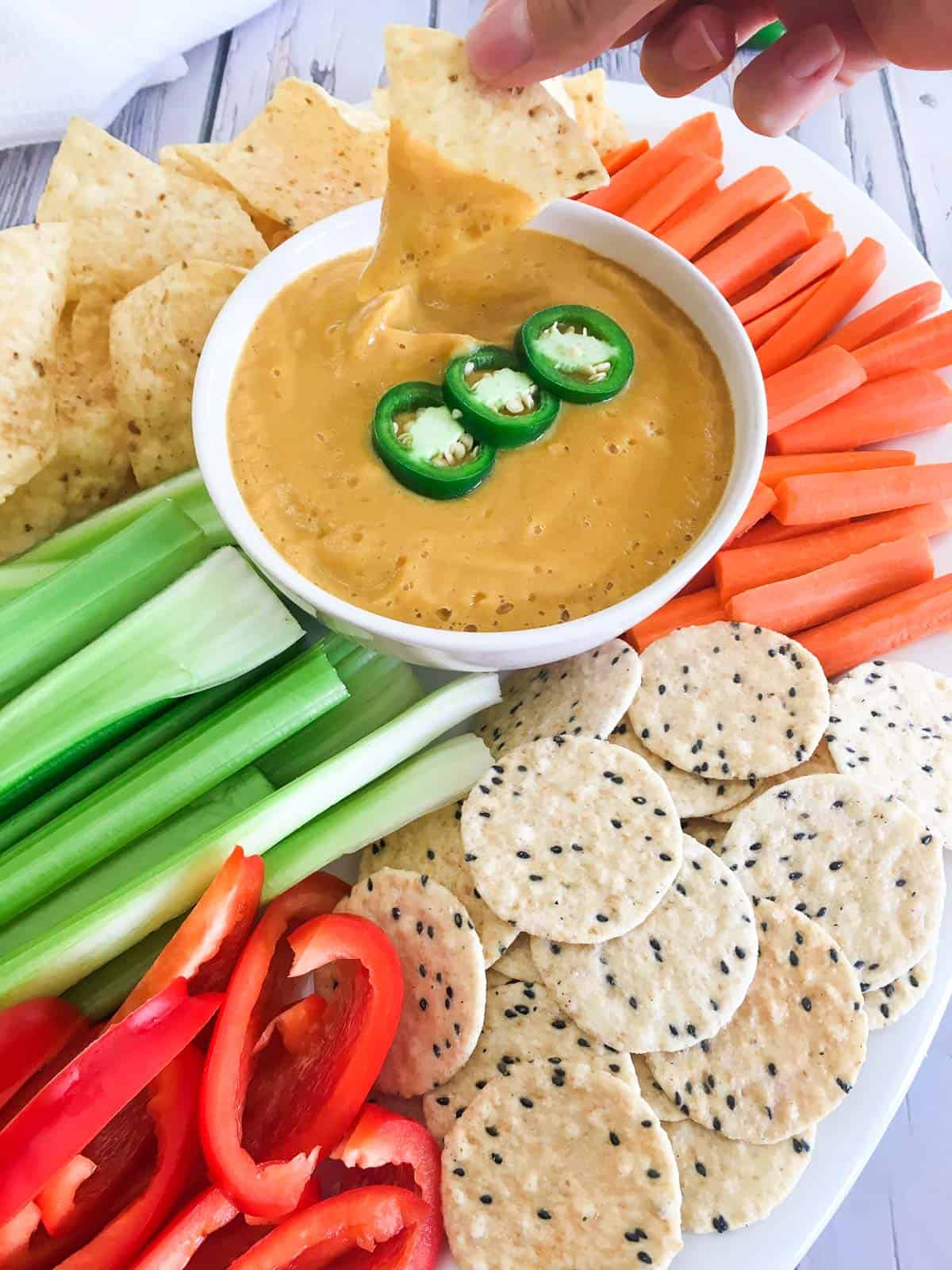 Tortilla chip dunked into cheese dip resting in white bowl with veggies and chips around the bowl.