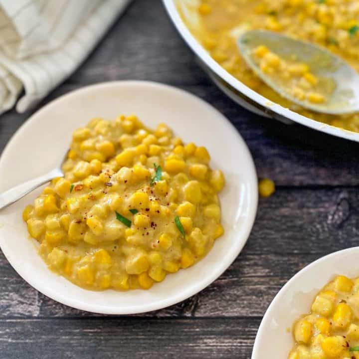 creamed corn in small white dish with spoon with pan of it in background.