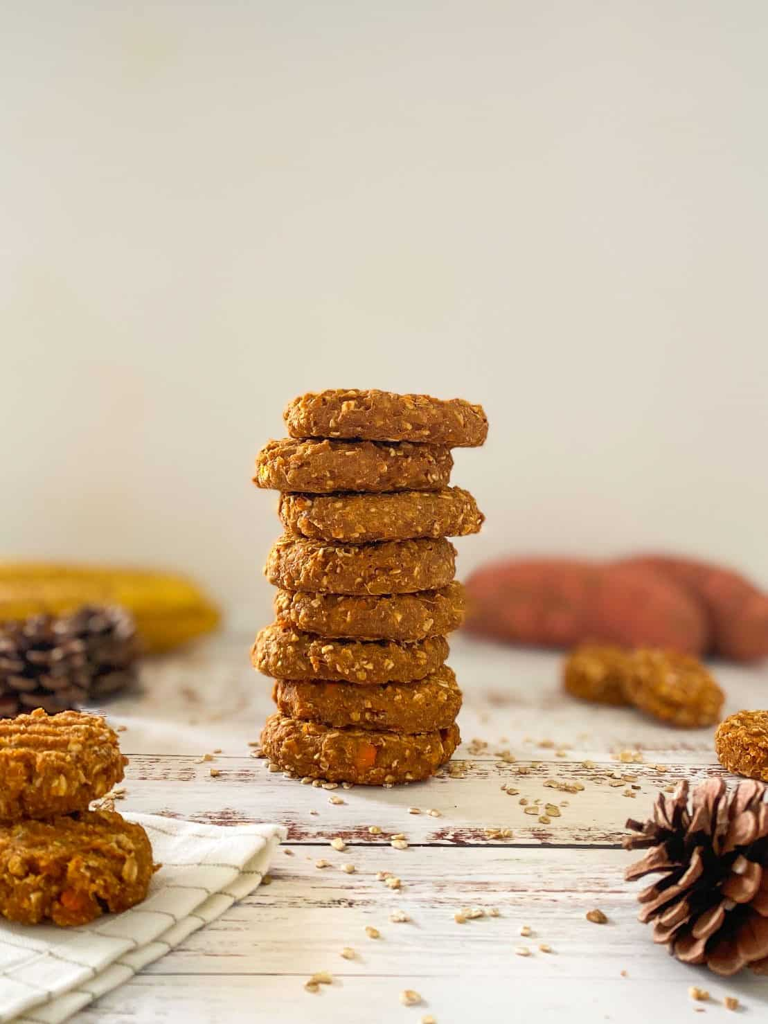 Tall stack of sweet potato cookies with more cookies scattered around it and bananas in the background.