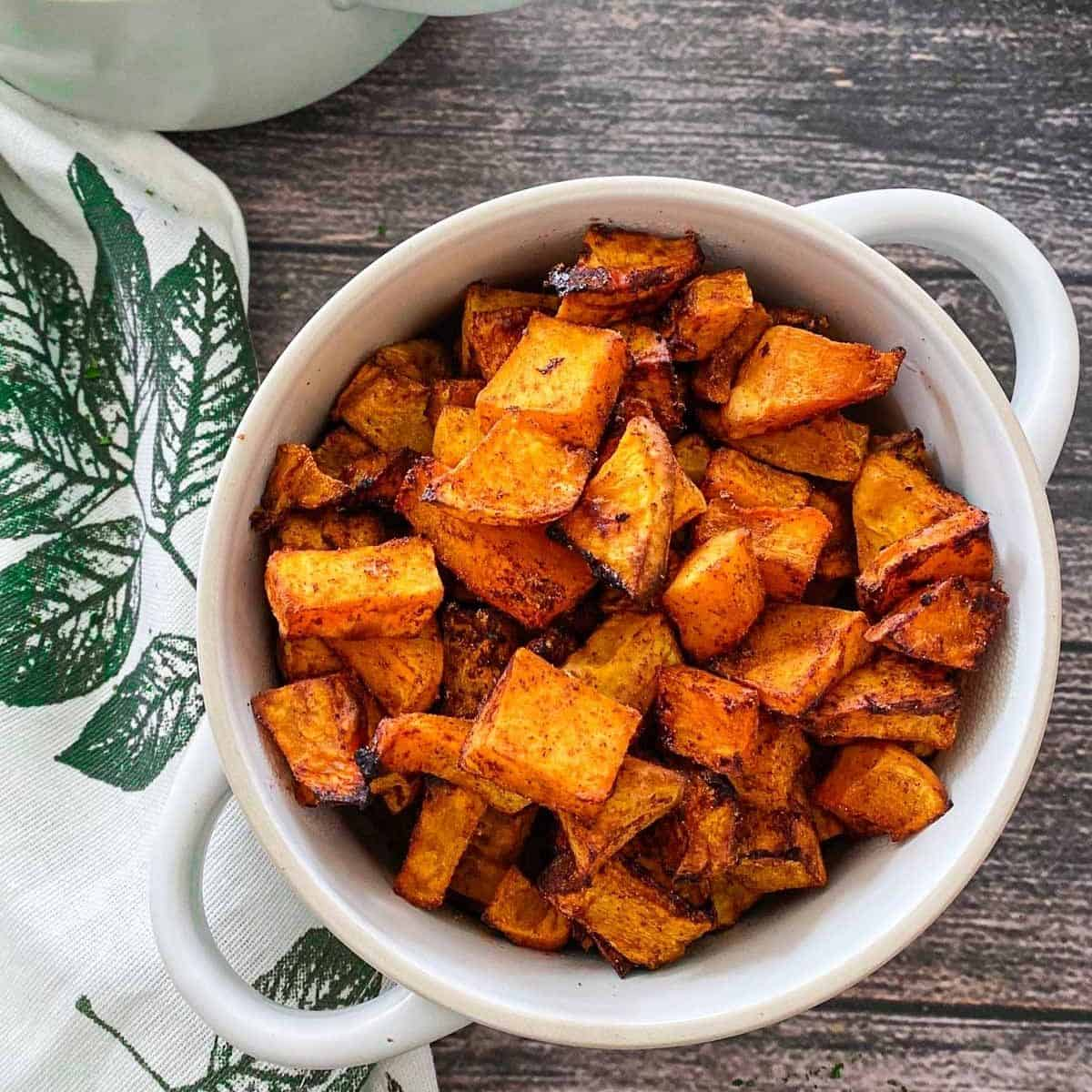 Two bowls with handles filled with air fried butternut squash,