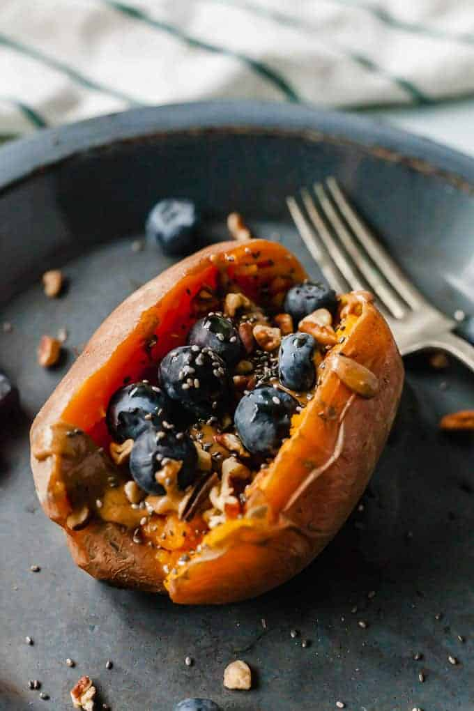 Sweet potato stuffed with peanut butter and topped with blueberries.