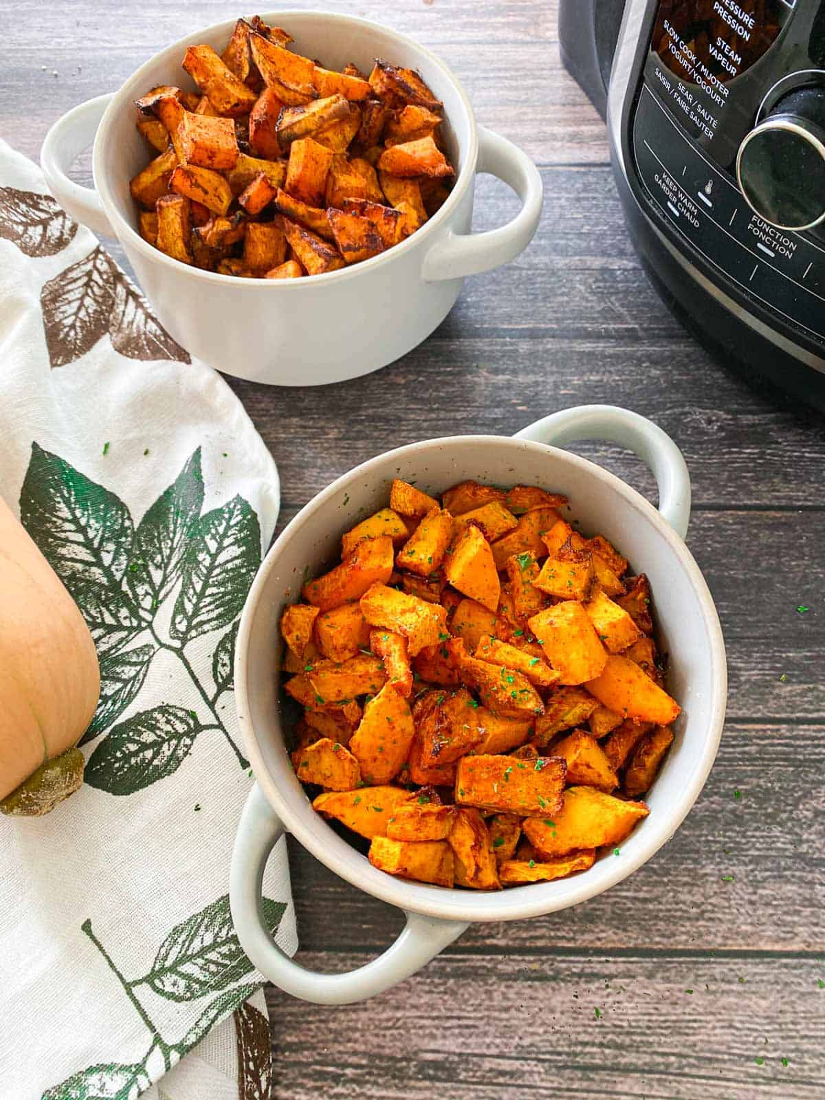 Two bowls of air fried butternut squash with air fryer in the background.