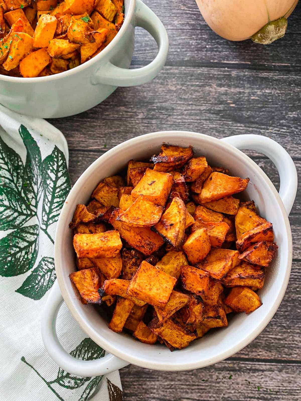 Two bowls of cooked, cubed butternut squash with seasoning.