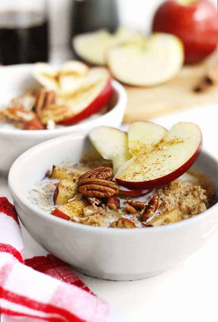 Bowl of oatmeal with apples and pecans on top.