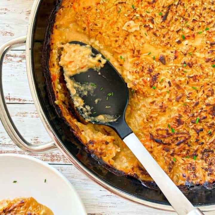 Hash brown casserole in round dish with ladle sitting inside.