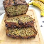 banana bread loaf on cutting board with two slices laying on their side.