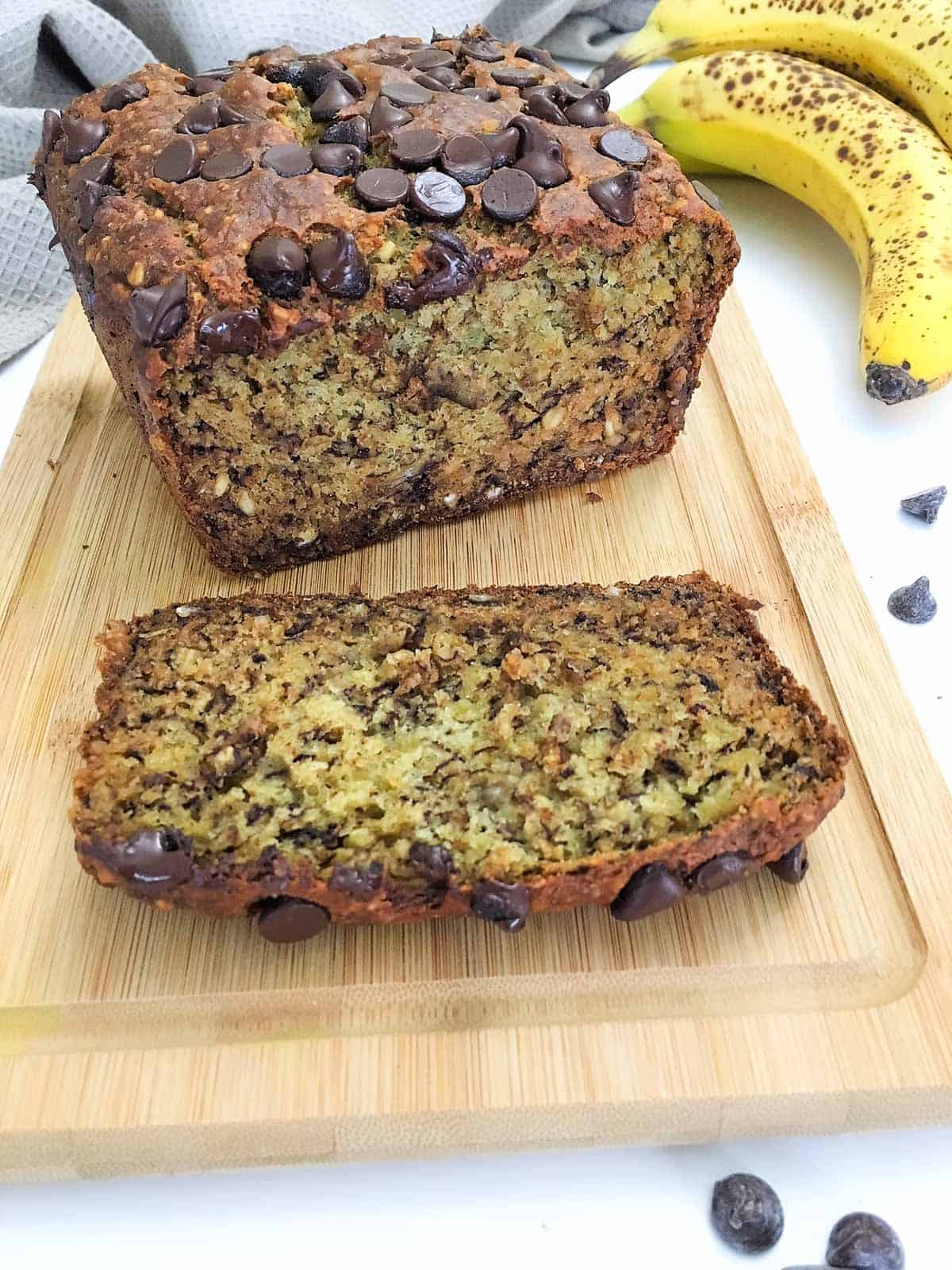Banana bread with chocolate chips on top on wooden cutting board with one slice cut.